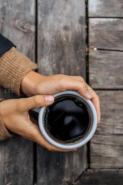 Hands holding fresh mug of coffee