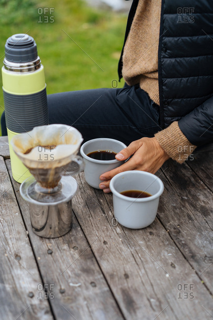 Person preparing hot coffee at picnic table