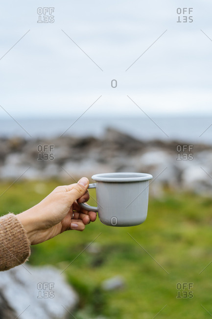 Person holding a mug in nature