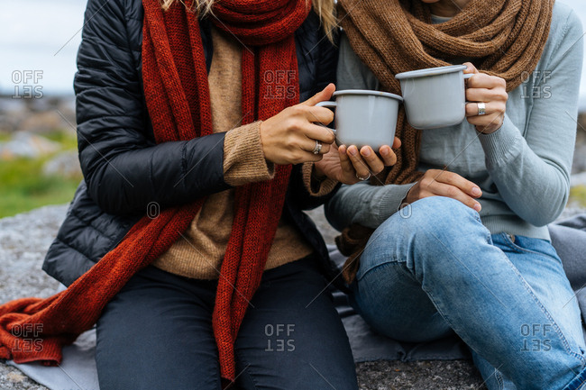 Two people drinking warm beverages outside