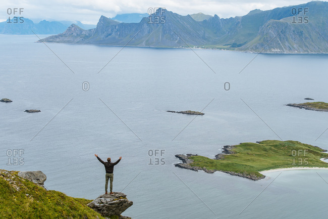 Man reaching arms up while on a cliff in the Lofoten Islands, Norway