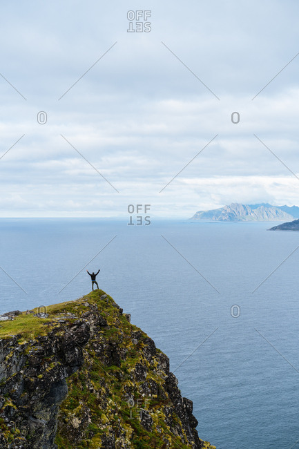 Man reaching arms up while overlooking sea on a cliff in the Lofoten Islands, Norway