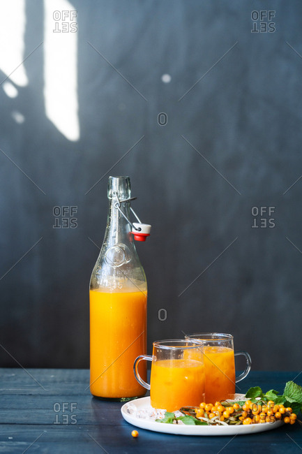 Fresh squeezed juice in a pitcher beside two glasses