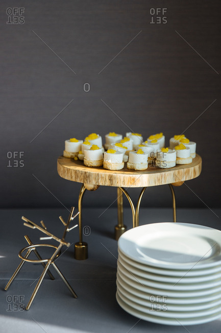 Gourmet dessert on a stand beside stack of plates