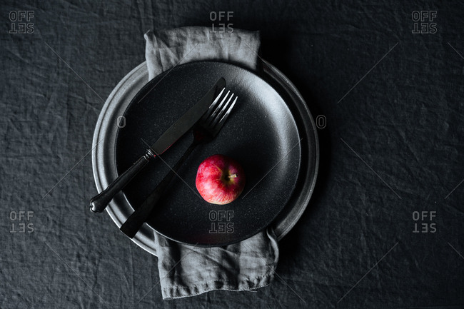 A single red apple on dark plate with silverware