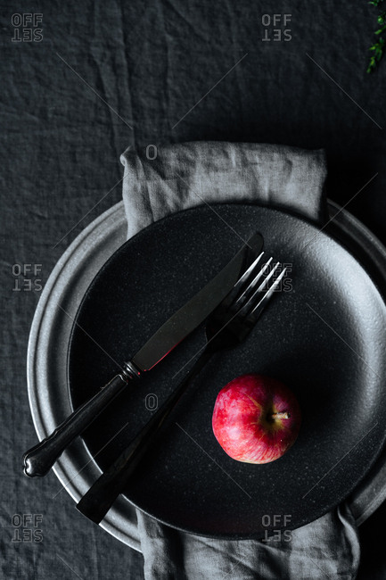 One red apple on dark plate with silverware