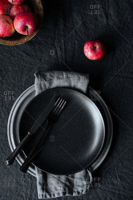 Red apple and dark plate with silverware