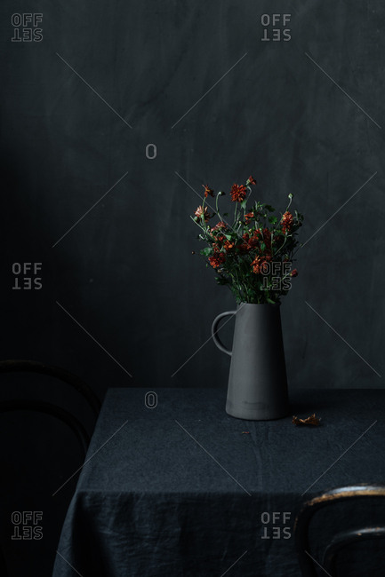 Orange flowers in a black pitcher
