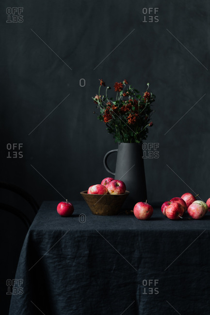Red apples on table beside flowers in a black pitcher
