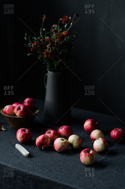 Red apples and knife on table beside flowers in a black pitcher