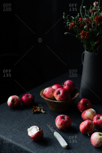 Apples and knife on table beside flowers