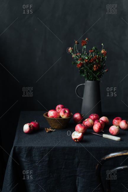 Bunch of red apples and knife on table beside flowers