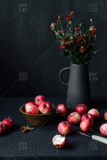 Several of red apples and knife on table beside flowers