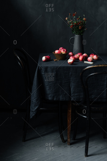 Table with several of red apples and knife beside flowers