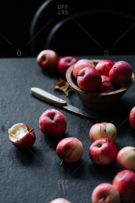 Several of red apples and knife on table
