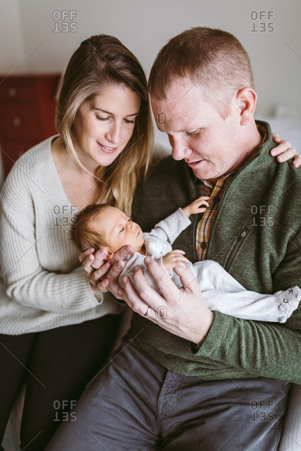 Mom and dad hold their newborn baby daughter while smiling