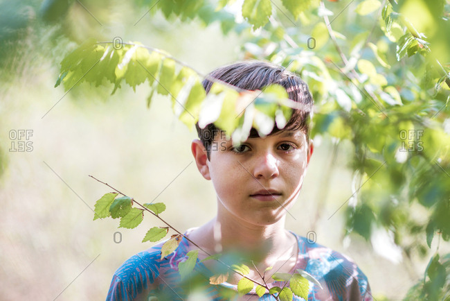 Young teen looking through branches and leaves deep in thought