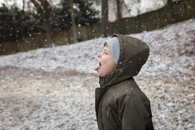 Boy catching snow on his tongue