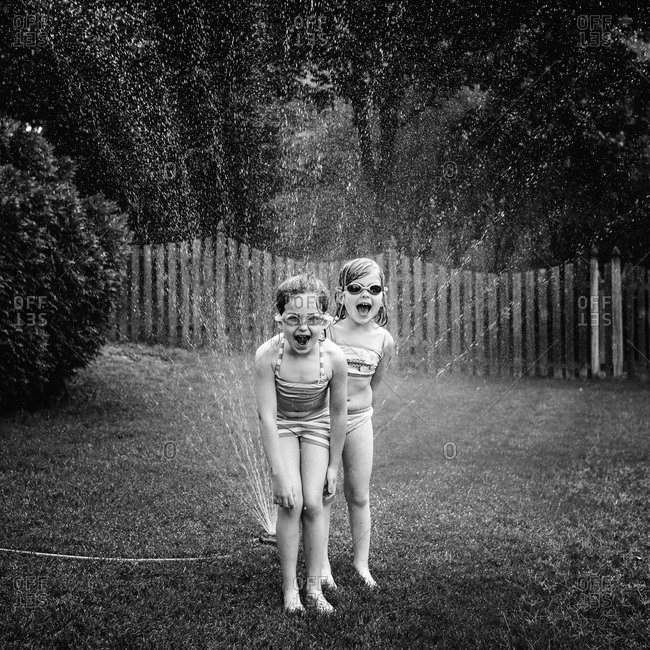 Girls playing in a sprinkler