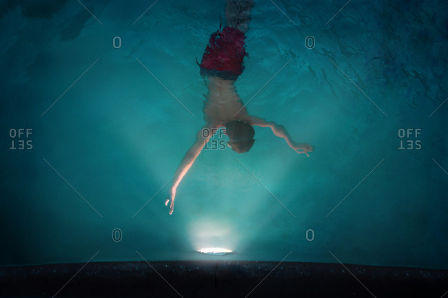 Boy swimming in a pool at night