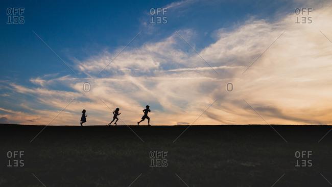 Three kids running on a hill