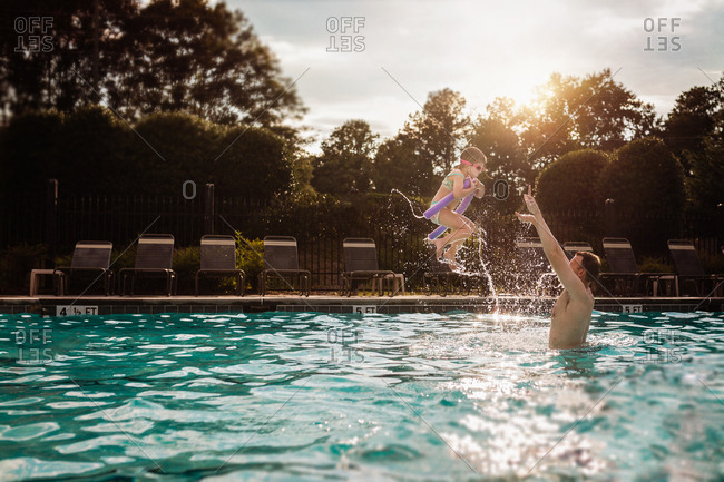 Dad throwing daughter in a pool