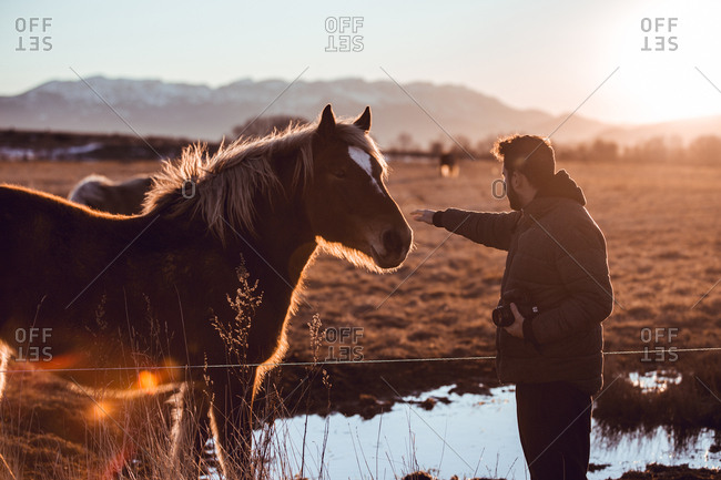 Side view of man touching a horse pasturing on meadow near water puddle between hills while holding a professional camera in sunny day in Cerdanya, France