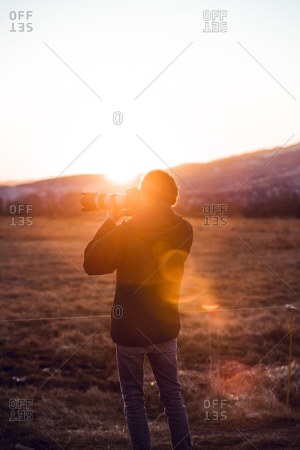 Back view of male taking photo of beautiful landscape between hills in sunny day in Cerdanya, France