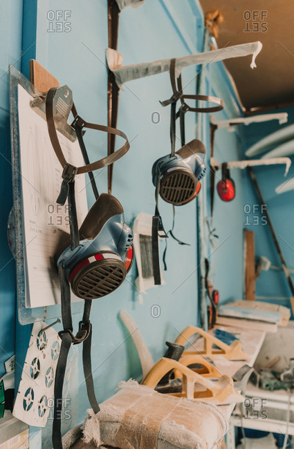 Breathers hanging near carpenter planes and other tools on workplace