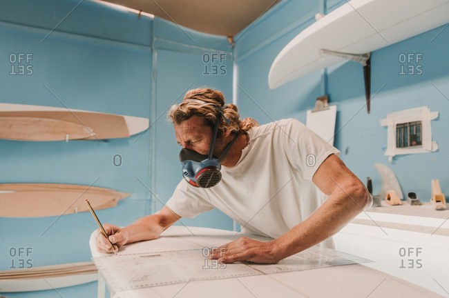 Side view of male in breather holding pencil and measuring surf board in workplace