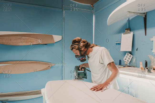 Man with tool sawing surf board in workshop