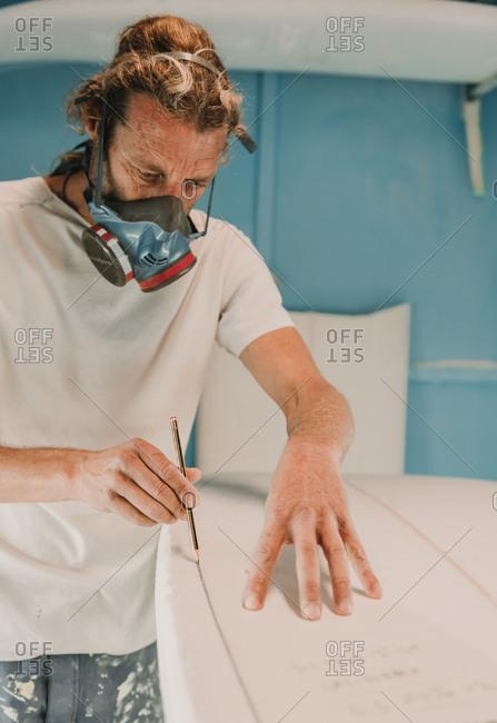 Man in respirator measuring surf board in workshop