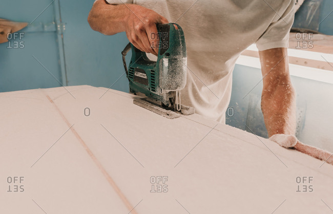 Crop male with electric jigsaw working and sawing wooden board in workplace