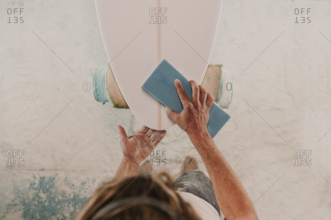Man in respirator polishing surf board in workshop
