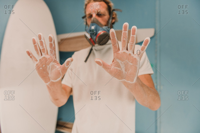 Male in breather showing palms in wooden dust near surf board in workplace