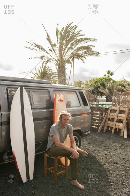 Man standing near surf boards and van