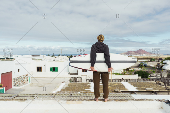 Back view of young guy in sweater standing with craft surf board on roof and looking at houses and stone hill