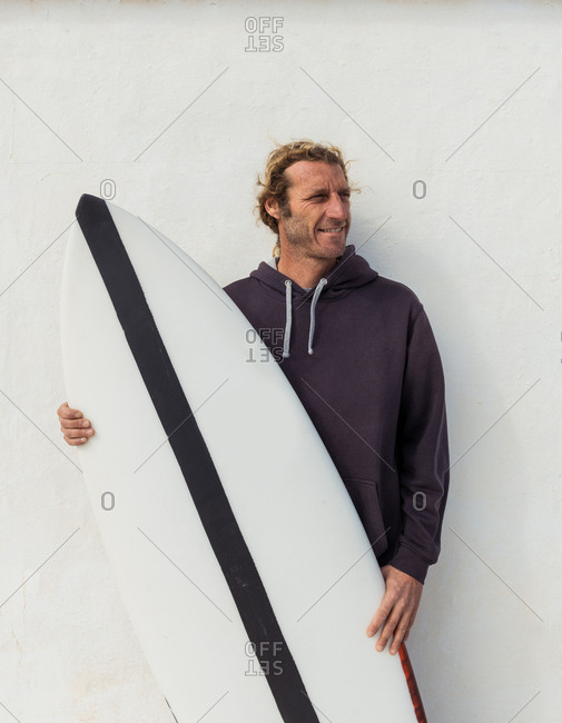 Handsome adult guy in sweater standing with craft surf board near white wall