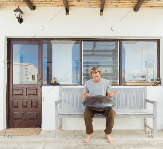 Barefooted guy in t-shirt sitting on seat with big hand drum near door and windows of building