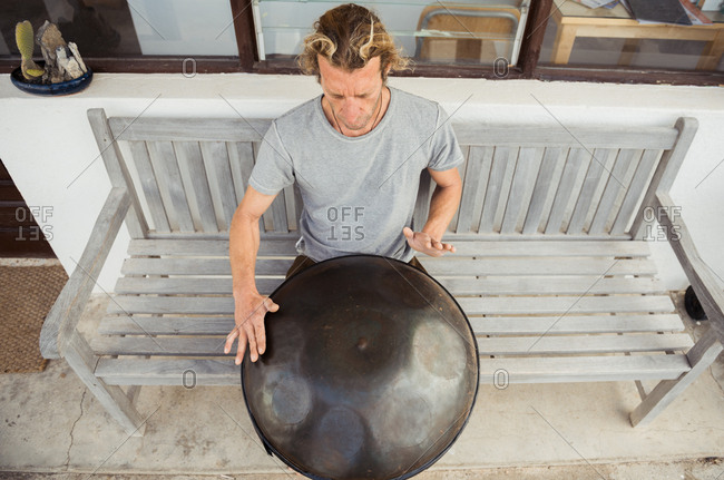 Blond man sitting on bench with big hand drum