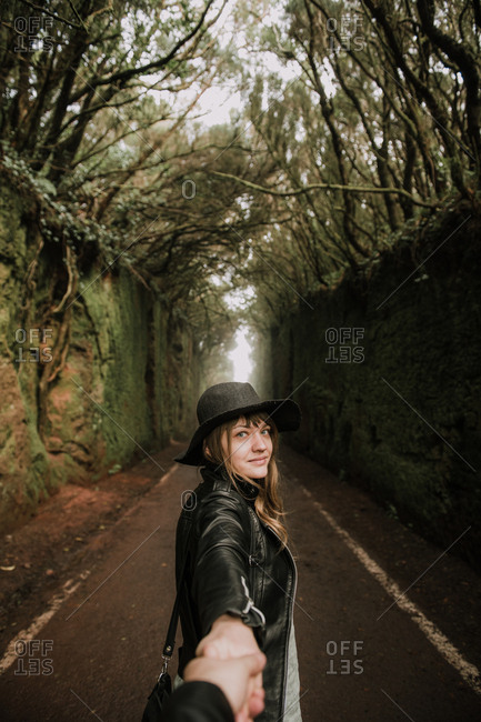 Side view of elegant lady in hat and leather jacket holding hand of person and standing on footpath between murk alley of high walls and woods