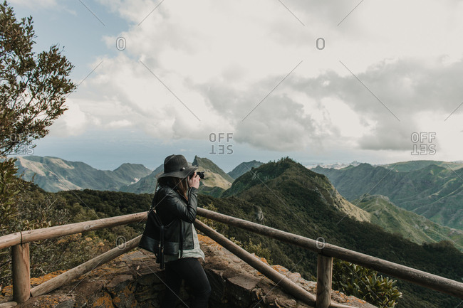 Side view of elegant lady in hat and leather jacket shooting on camera amazing view of peaks of hills and cloudy sky