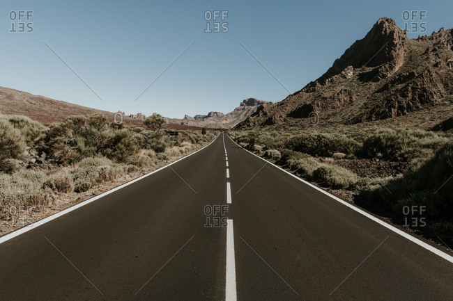 Perspective view to asphalt road in dry land leading to mountains