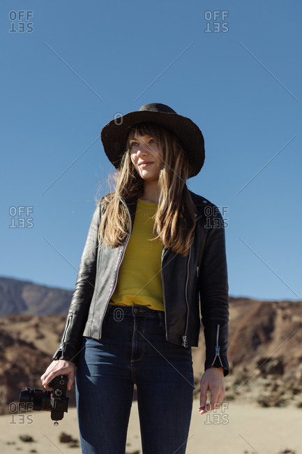 Female photographer standing with camera and looking at hills in desert
