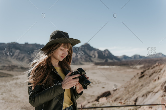 Female photographer standing and looking at the camera in desert
