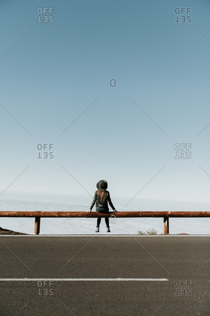 Back view of tourist woman sitting on wooden fence at the edge of the hill