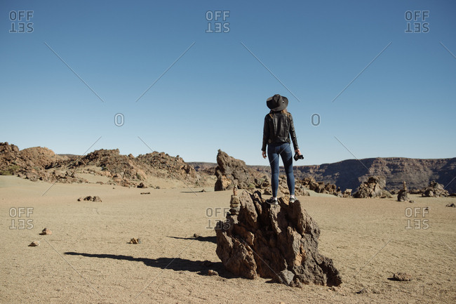 Unrecognizable tourist standing on the top of the rock in the desert in cloudless day