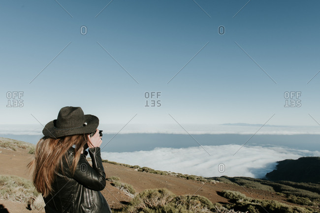 Back view of woman with photo camera standing on the top of the hill and looking at cloudscape