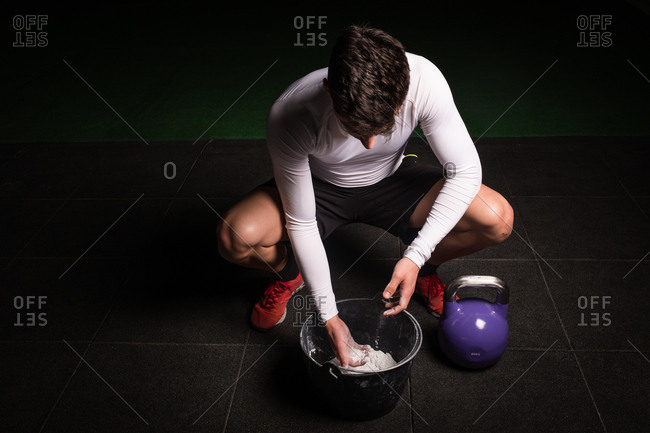 From above athletic young guy in sportswear chalking hands for lifting big kettle bell in gym