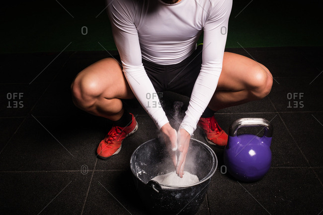 From above athletic crop young guy in sportswear chalking hands for lifting big kettle bell in gym